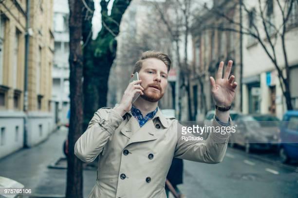若い男の手を振って、路上で携帯電話で話しています。 - トレンチコート ストックフォトと画像