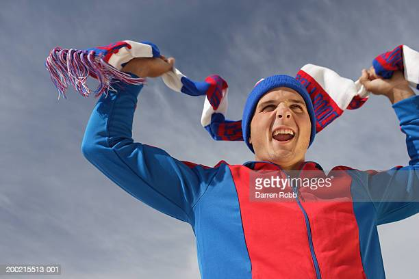 Young man waving scarf above head, outdoors, low angle view