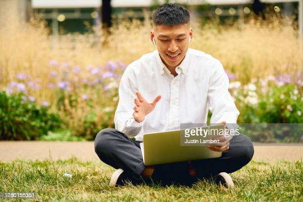 young man waving while on a video call on his laptop own the park - working stock pictures, royalty-free photos & images