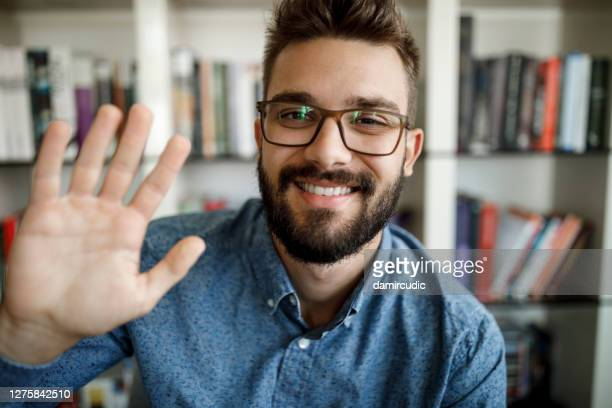 young man waving with hand on video call at home office - greeting stock pictures, royalty-free photos & images