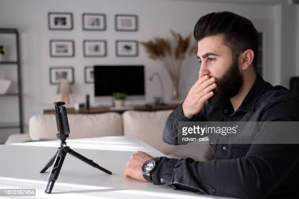 jonge mens die met hand op videogesprek bij huisbureau zwaait - flexplekken stockfoto's en -beelden