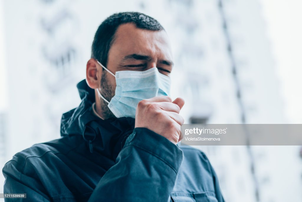 Young man wear face mask and coughing outdoors. : Stock Photo