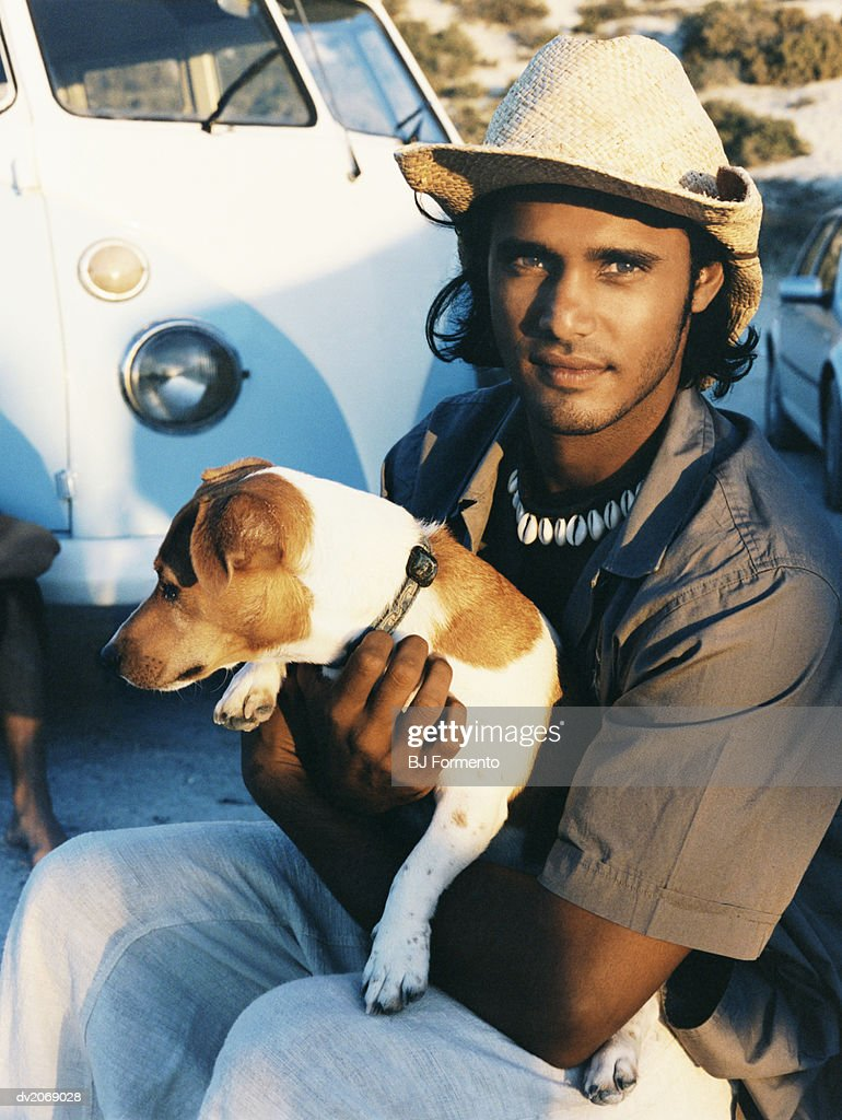 Young man Wearing a Cowboy Hat Holding a Jack Russell : Stock Photo
