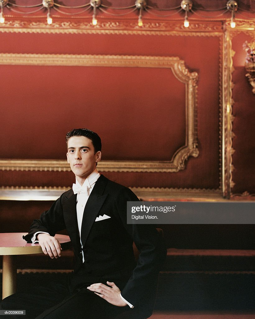 Young Man Wearing a Dinner Jacket Sitting at a Table : Stock Photo