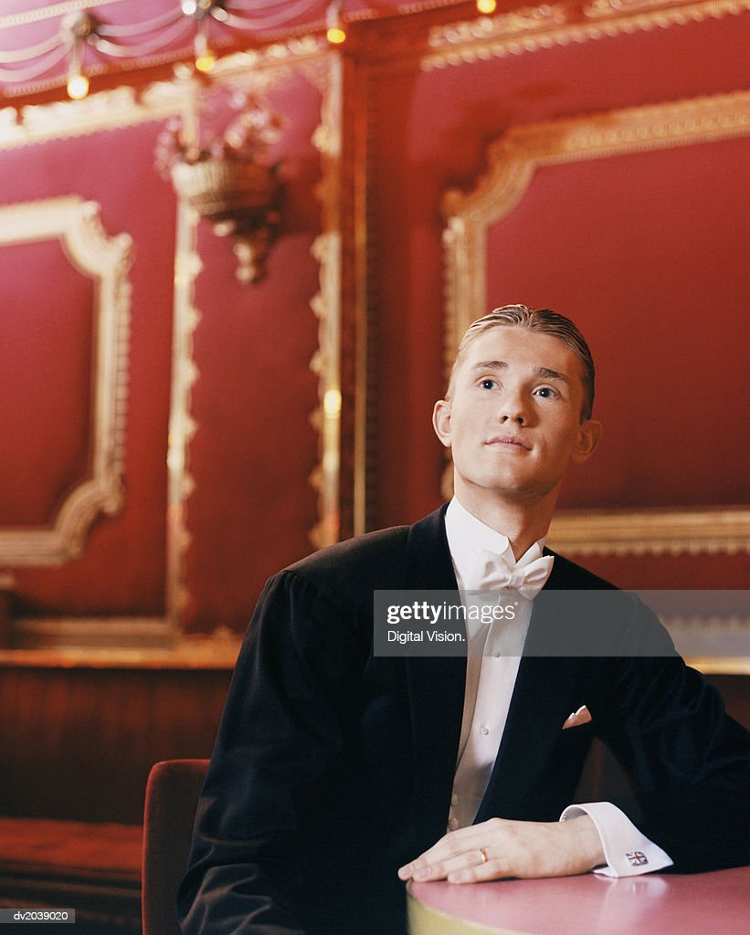 Young Man Wearing a Dinner Jacket Sitting at a Table Watching Ballroom Dancing : Stock Photo