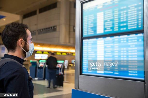 young man wearing a face mask checking his flight on the monitor screen board - stellalevi stock pictures, royalty-free photos & images