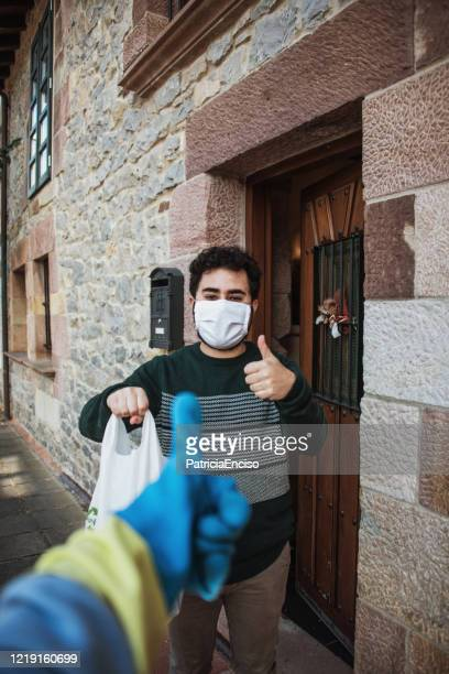 young man wearing a face mask receiving a bag with food - avoidance stock pictures, royalty-free photos & images
