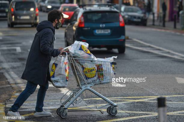 Young man wearing a face mask seen pushing a shopping cart in Ranelagh, Dublin, during Level 5 Covid-19 lockdown. On Sunday, February 14 in Ranelagh,...