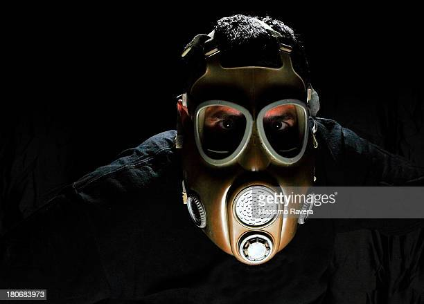 A young man wearing a gas mask