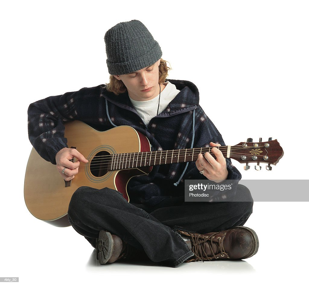 young man wearing a gray hat jacket and dark pants sits on the ground while playing a guitar : Stock Photo