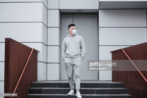 young man wearing a gray tracksuit and with his protective mask on - trainingsanzug stock-fotos und bilder