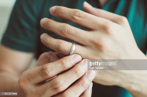 a young man wearing a green shirt is holding his wedding ring - white gold stock pictures, royalty-free photos & images