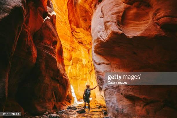 young man wearing a hat, exploring a slot canyon in kanarra fall, utah - utah stock pictures, royalty-free photos & images