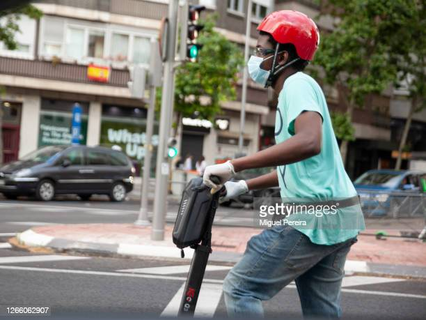 Young man wearing a helmet and a face mask rides an electric scooter on June 7 in Madrid, Spain.