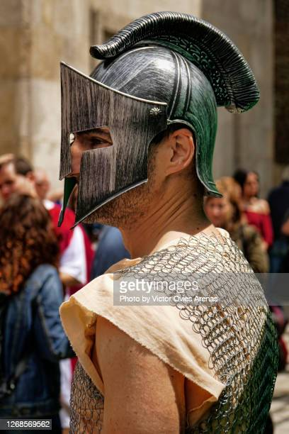 young man wearing a helmet and roman era soldier clothes during the annual arde lucus historical reenactment festival - victor ovies fotografías e imágenes de stock