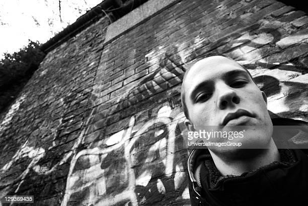 Young man wearing a hoodie, Stood by Graffiti, UK 2005