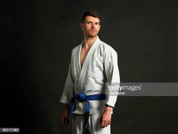 young man wearing a judo uniform looking at the camera - judo stock pictures, royalty-free photos & images