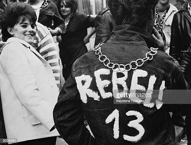 A young man wearing a painted Rebel 13 jacket and a large medallion chain attends a Teddy Boy convention in Zurich