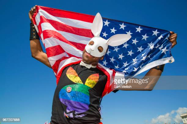 A young man wearing a Playboy bunny tshirt and white rabbit mask holds an American flag over his shoulders during the Brighton Pride Parade on 6th...