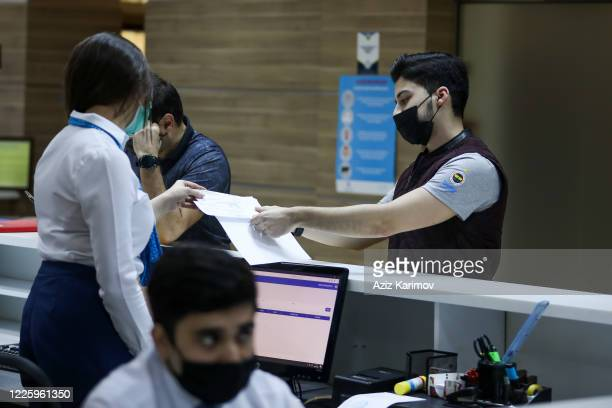 A young man wearing a protective facemask and show document inside ASAN service in Baku on May 20 2020 in Baku Azerbaijan The coronavirus outbreak...