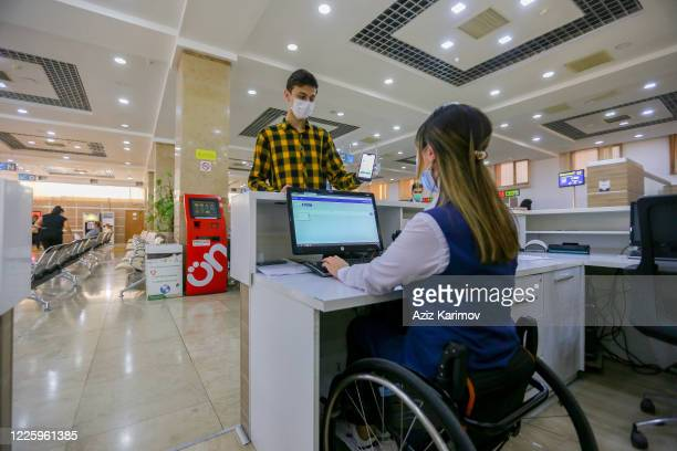 A young man wearing a protective facemask and show online document inside ASAN service in Baku on May 20 2020 in Baku Azerbaijan The coronavirus...