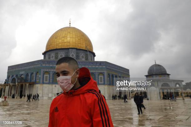 Young man wearing a protective mask as a measure of protection against the coronavirus COVID-19, walks in front of the Dome of the Rock mosque inside...
