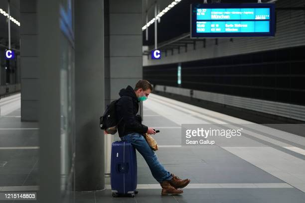 A young man wearing a protective mask who said he did not mind being photographed waits on a train platform at nearlydeserted Hauptbahnhof main...