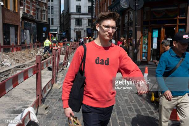 Young man wearing a red sweatshirt with the word 'Dad' printed on it in London, United Kingdom. One can imagine this is a piece of ironic fashion in...