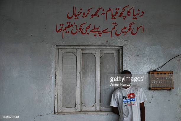 Young man, wearing a shirt of YouTube, stands at a local Dhaba or restaurant on which the Urdu couplet above says, 'Don't think of this world's life...