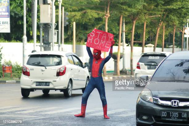 Young man wearing a Spiderman costume takes to the streets to campaign for healthy living, stay home, and wear a mask to prevent the transmission of...
