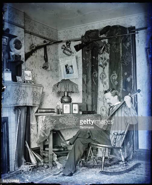 Young man wearing a striped blazer seated in a Victorian room playing a Balalaika Photograph ca 1890