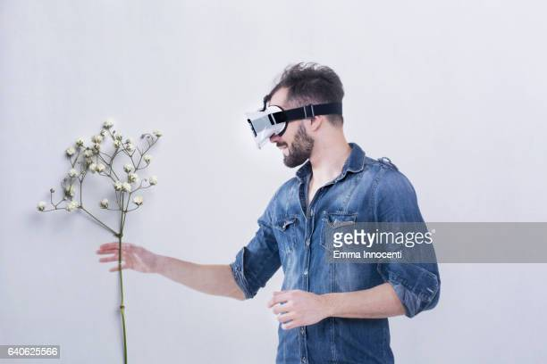 Young man wearing a virtual reality headset touching a plant