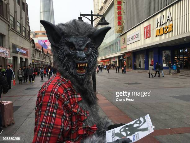 A young man wearing a wolf mask stands on street distributing posters of a horror experience space established by him and his friend In China youth...