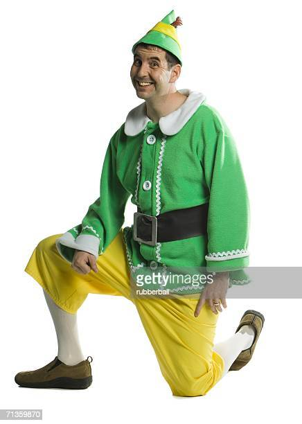 Young man wearing an elf costume and kneeling on the floor