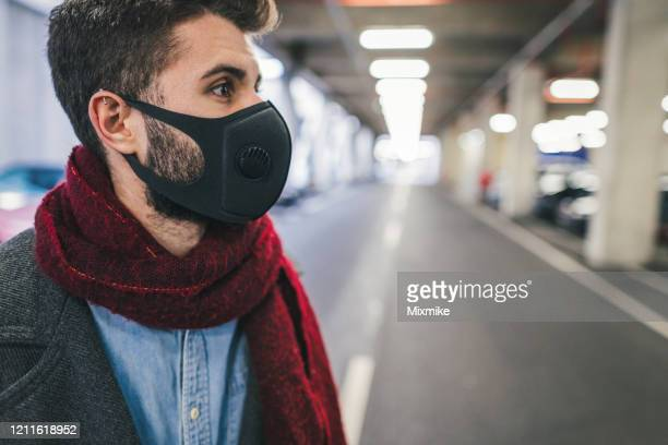 young man wearing anti-smog air pollution mask for protection in the city - air respirator mask stock pictures, royalty-free photos & images