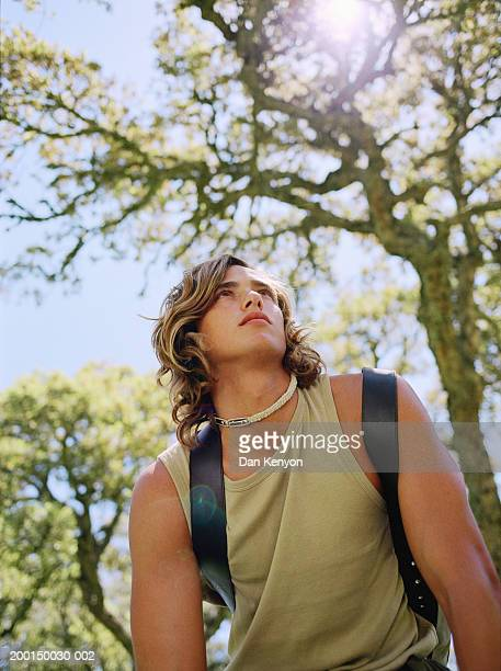 Young man wearing backpack, outdoors, low angle view