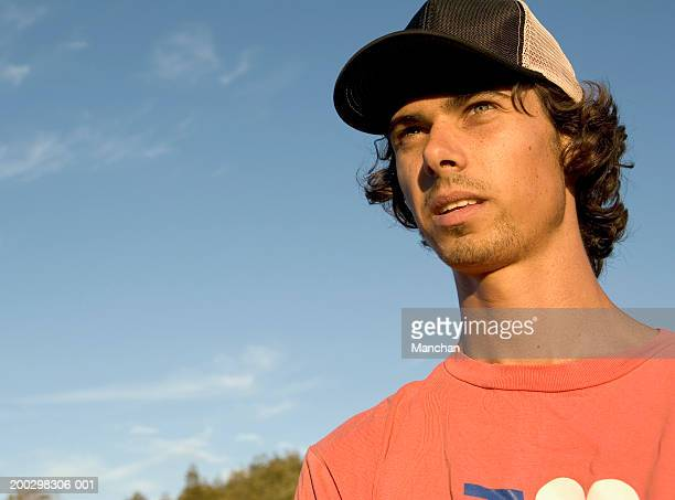 young man wearing baseball cap, outdoors, low angle view, close-up - trucker's hat stock pictures, royalty-free photos & images