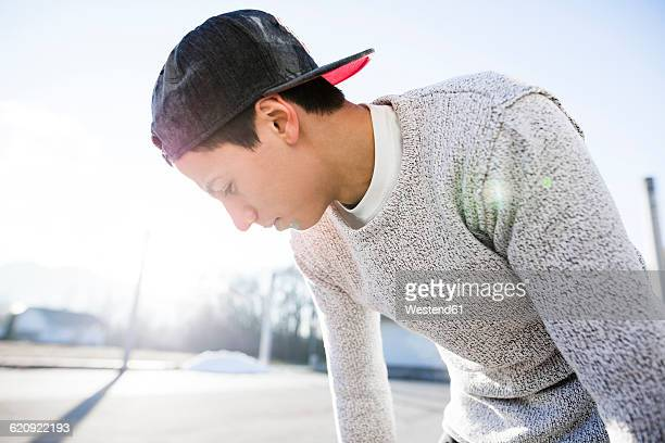 Young man wearing basecap in backlight