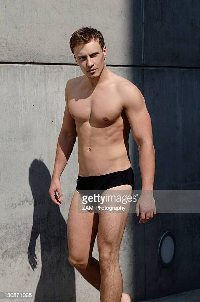 young man wearing bathing trunks, walking in front of a concrete wall - zwembroek stockfoto's en -beelden