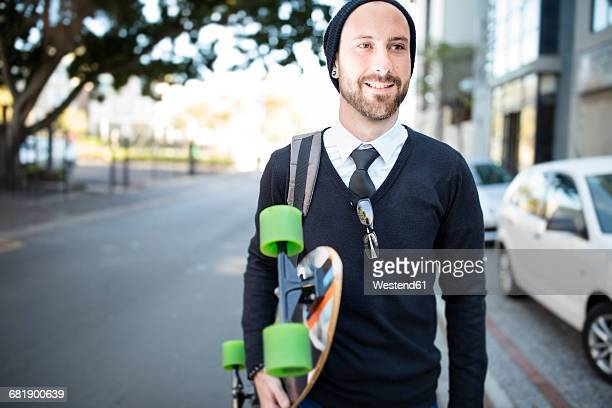 Young man wearing beanie holding skateboard