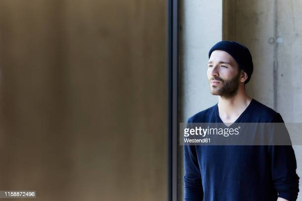 young man wearing beanie looking out of window - só homens jovens imagens e fotografias de stock