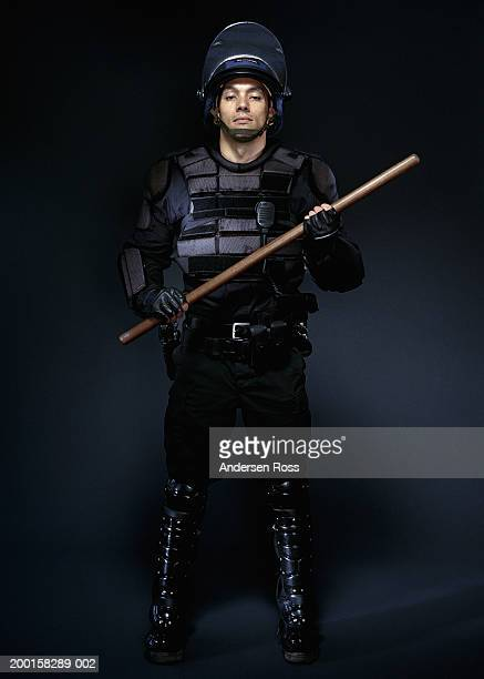 young man wearing body armor, holding baton, portrait - riot police stock pictures, royalty-free photos & images