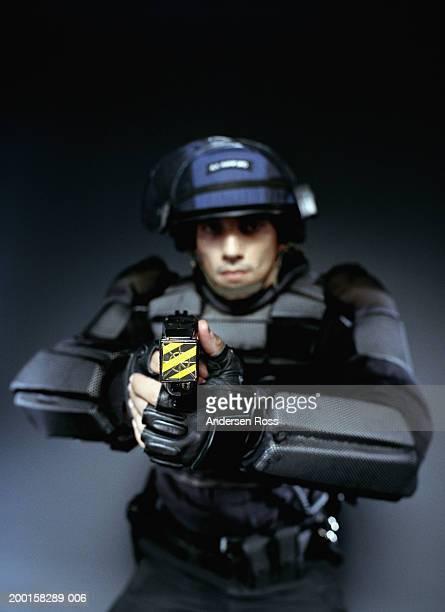 young man wearing body armor, pointing stun gun (focus on stun gun) - 機動隊 ストックフォトと画像