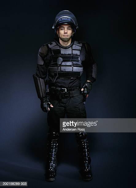 young man wearing body armor, reaching for handgun, portrait - 機動隊 ストックフォトと画像