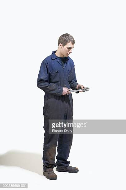 Young man wearing boiler suit holding wrench