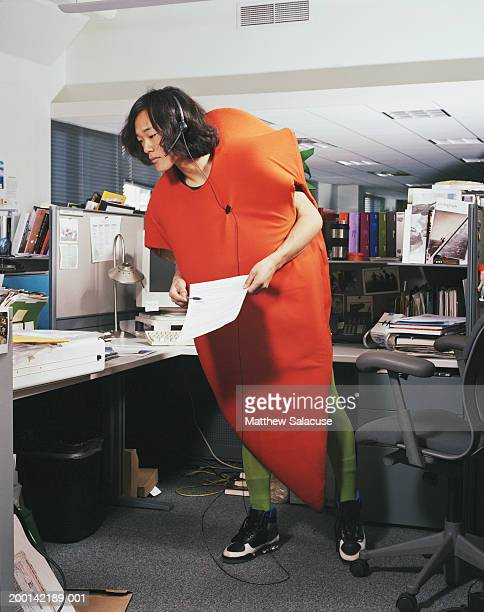 Young man wearing carrot costume in office