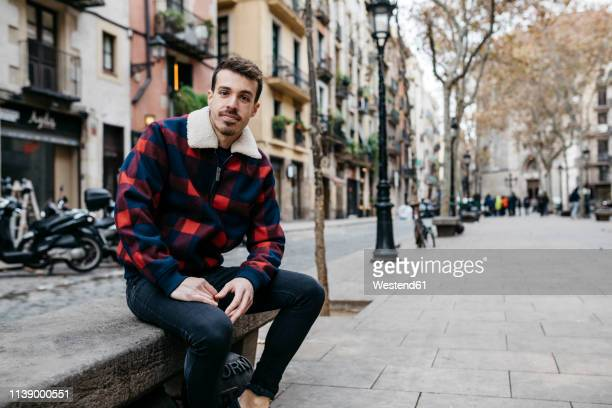 young man wearing casual clothes sitting on a bench in the city - pedestrian zone stock pictures, royalty-free photos & images