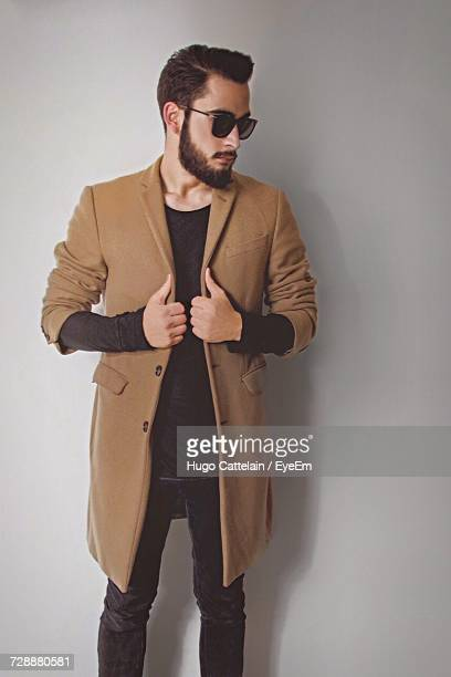 Young Man Wearing Coat Against Wall
