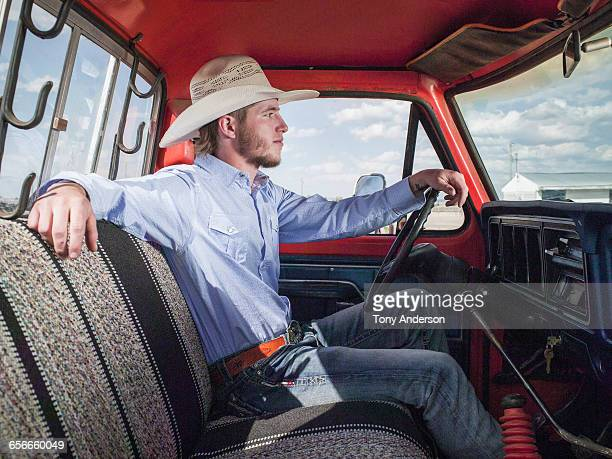 Young man wearing cowboy hat in pick up truck
