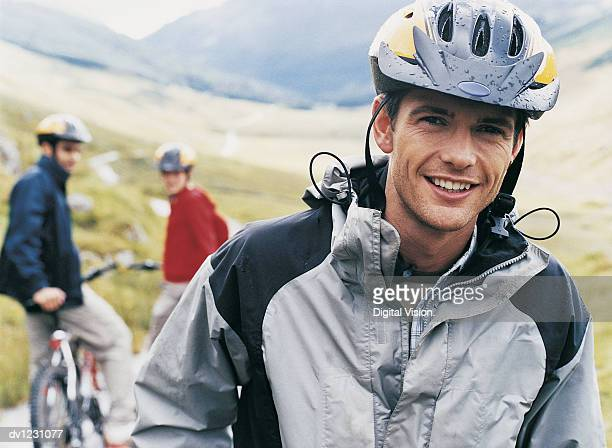 Young Man Wearing Cycling Helmet is Waited for by his Friends